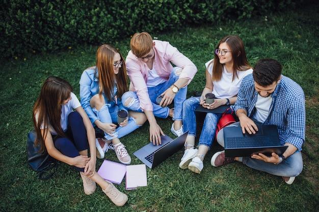 Een groep studenten zit op een campus. cursuswerk herhalen op een laptop. zittend op het gras.