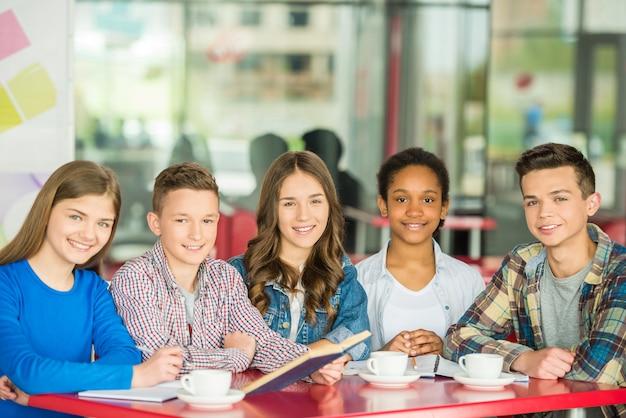Een groep tieners zitten aan de tafel in café.