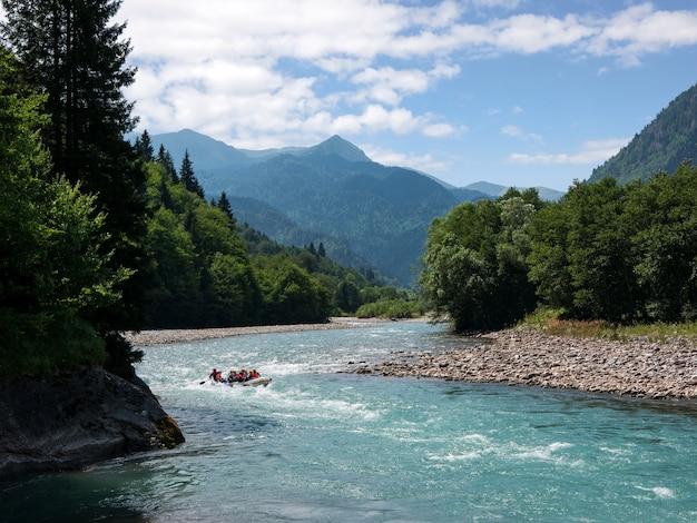 Een groep toeristen raften de rivier af tegen een geweldig berglandschap
