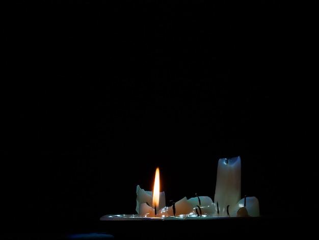 Een groep uitgebrande kaarsen waarvan één nog steeds brandt in het donker