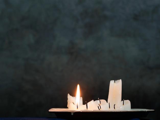 Een groep uitgebrande kaarsen waarvan één nog steeds brandt