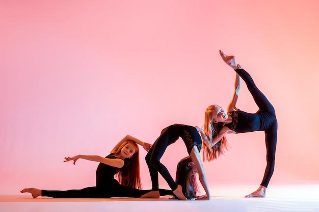 Een groep van drie balletmeisjes met lang golvend haar in zwarte strakke pakken dansen op een rode achtergrond