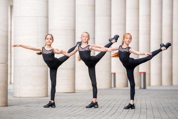 Een groep van drie kleine ballerina's in zwarte nauwsluitende kostuums danst tegen een achtergrond van het stadsbeeld.