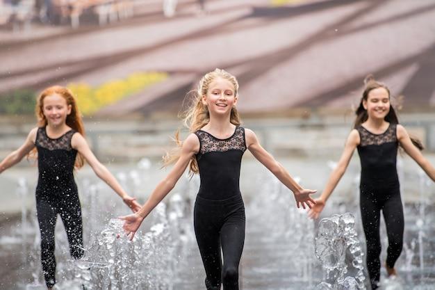 Een groep van drie kleine ballerina's in zwarte nauwsluitende pakken rent op een warme dag te midden van klaterende fonteinen op de toeschouwer af tegen de achtergrond van een stadsbeeld.