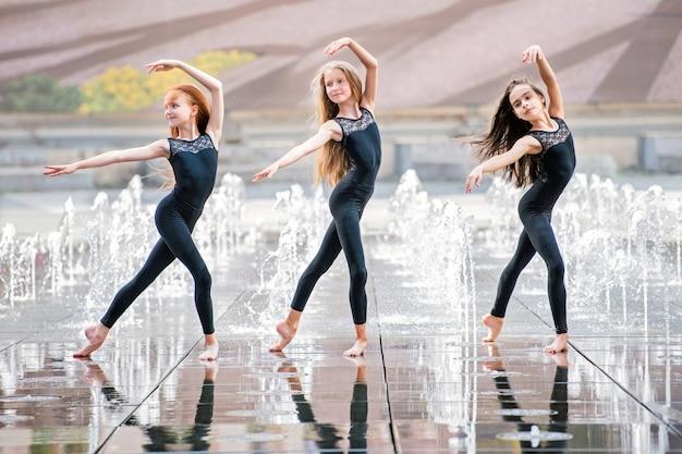 Een groep van drie kleine ballerina's in zwarte strakke pakken dansen op een warme dag tegen de achtergrond van stadsfonteinen.