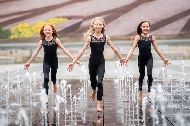 Een groep van drie kleine ballerina's in zwarte strakke pakken rennen naar de kijker te midden van spattende fonteinen tegen de achtergrond van een stadsbeeld op een warme dag.