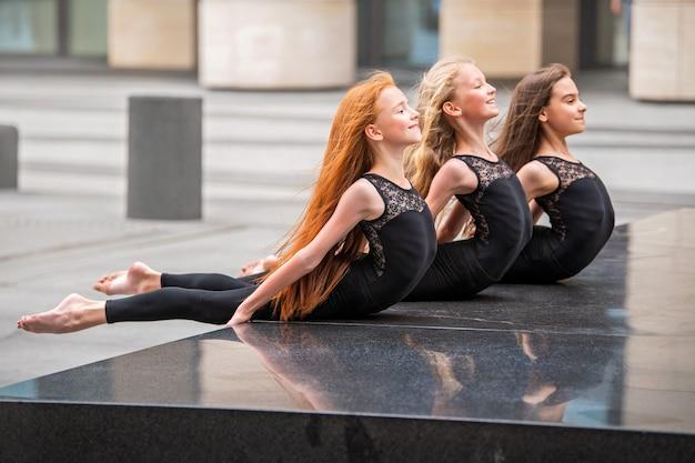 Een groep van drie tienermeisjes dansers gymnasten in zwarte strakke pakken met lang golvend haar poseren tegen de achtergrond van een stadsgezicht.