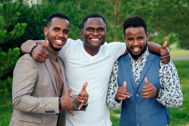 Een groep van drie zwarte mannen in stijlvolle pakken een vergadering in een zomerpark. afro-amerikanen vrienden spaanse zakenman groet pose teamwork buitenshuis
