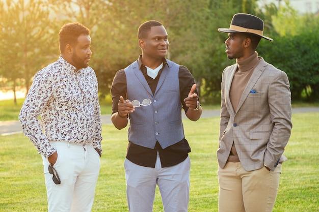 Een groep van drie zwarte mannen in stijlvolle pakken in een zomerpark. afro-amerikanen vrienden spaanse zakenman communiceren buitenshuis.