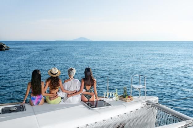 Een groep van vier jonge vrouwen die elkaar omhelzen, kijken naar de horizon van de zee