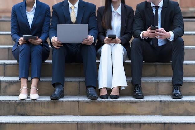 Een groep van vier zakenlui die met telefoons en computer zitten