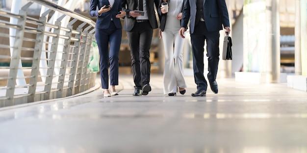 Een groep van vier zakenmensen loopt en praat met elkaar