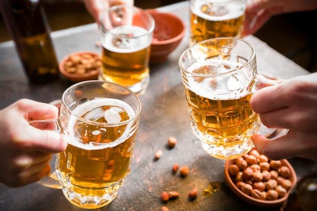 Een groep vrienden drinkt bier van mokken in een bar aan tafel.