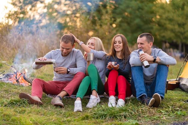 Een groep vrienden geniet van een warm drankje uit een thermosfles, op een koele avond bij een vuur in het bos. leuke tijd kamperen met vrienden