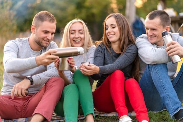 Een groep vrienden geniet van een warm drankje uit een thermosfles, op een koele avond bij een vuur in het bos.