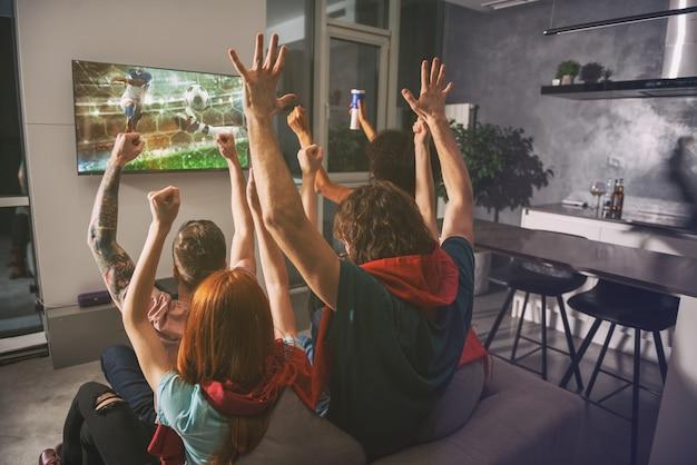 Een groep vrienden kijkt samen naar het spel op televisie en verheugt zich