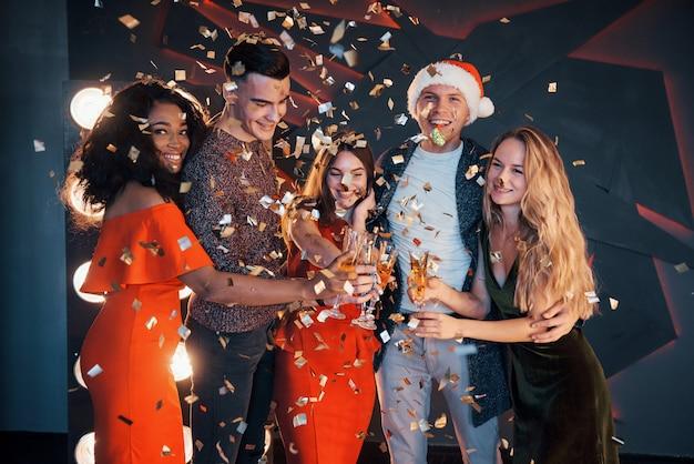 Een groep vrienden poseren en plezier maken met sneeuwmannen en champagne. nieuwjaarsviering.
