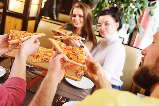 Een groep vrienden praten en glimlachen in een café en eten pizza.