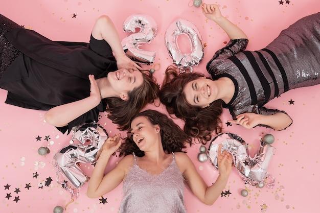 Een groep vriendinnen heeft plezier op een kerstfeest, liggend op een roze achtergrond met ballonnen van de nummers 2022, bovenaanzicht.