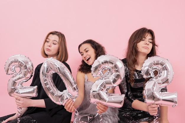Een groep vriendinnen op een roze achtergrond met zilveren folieballonnen in de vorm van de nummers 2022 ervaart verschillende emoties en viert het nieuwe jaar.