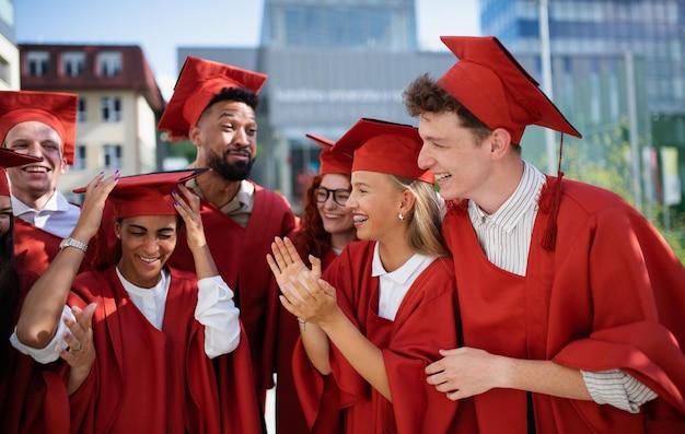 Een groep vrolijke universiteitsstudenten die buiten vieren, afstuderen concept.