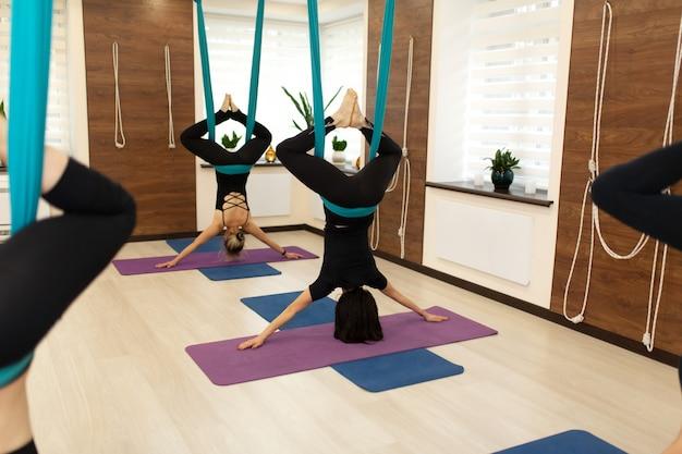 Een groep vrouwen hangt ondersteboven in een hangmat. vlieg yogales in de sportschool. fit en wellness levensstijl