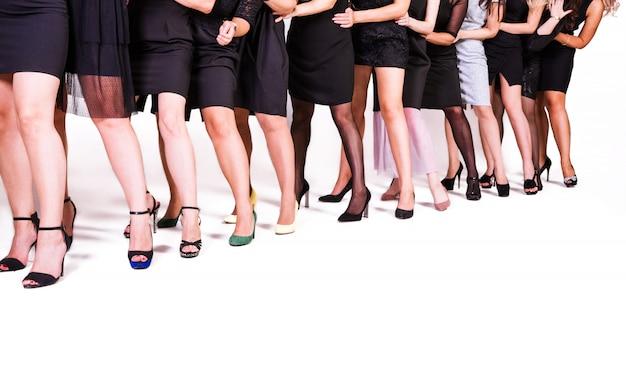 Een groep vrouwen in zwarte jurken en schoenen