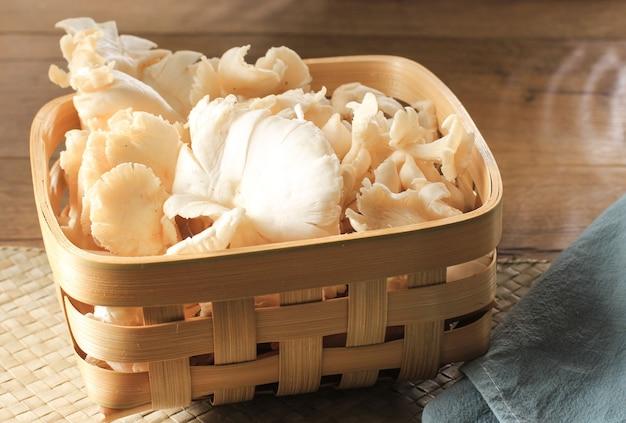 Een groep witte oesterzwammen op rieten mand op bruine houten tafel klaar om te koken in de keuken