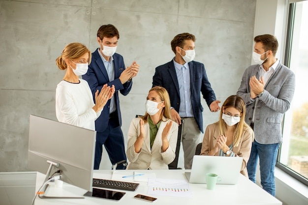 Een groep zakenmensen vergadert en werkt op kantoor en draagt maskers als bescherming tegen coronavirus