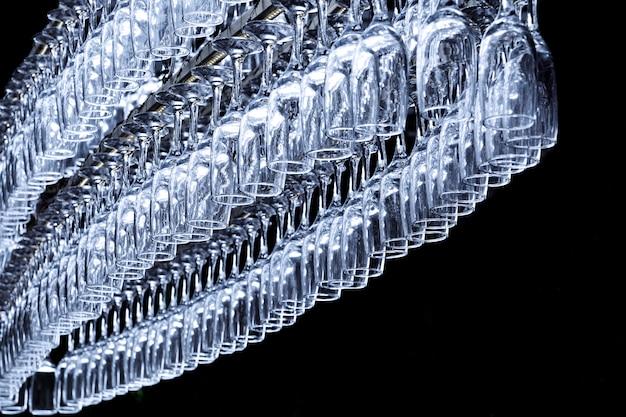 Een groot aantal glazen in de vorm van een ovaal hangen aan de houder aan de bar op een donkere achtergrond.