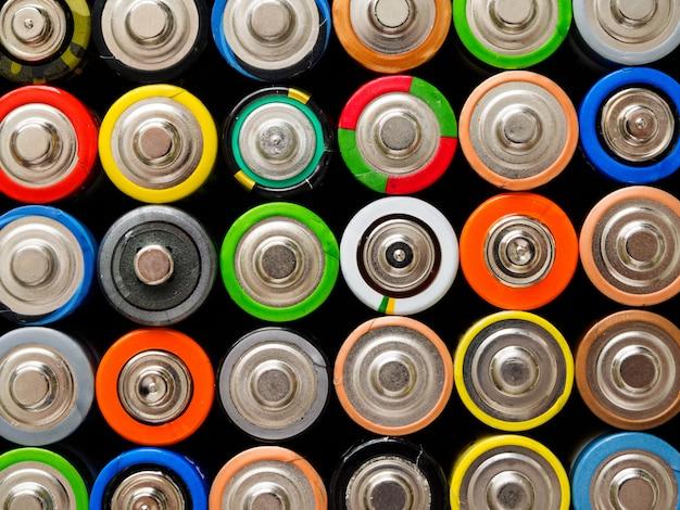 Een groot aantal oude aa-batterijen in verschillende kleuren.