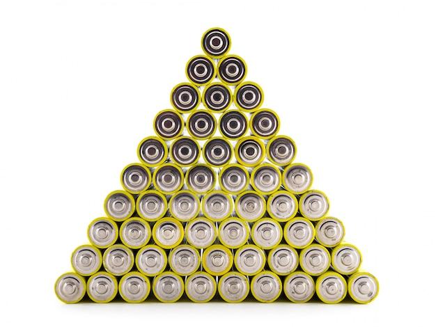 Een groot aantal oude aa-batterijen van gele kleur zijn gebouwd in de vorm van een piramide. batterijen