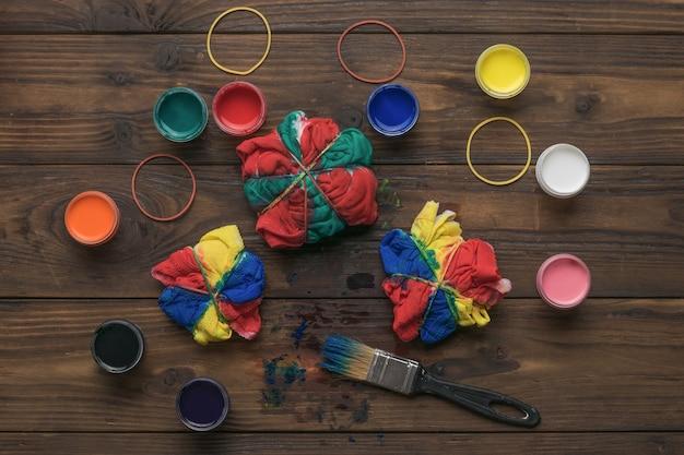 Een groot aantal stoffen verven en penselen met stof op een houten oppervlak. stof beitsen in tie-dye-stijl.