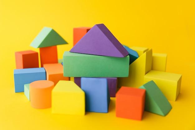Een groot aantal verschillende veelkleurige en verschillende vormen geometrische vormen op een gele achtergrond