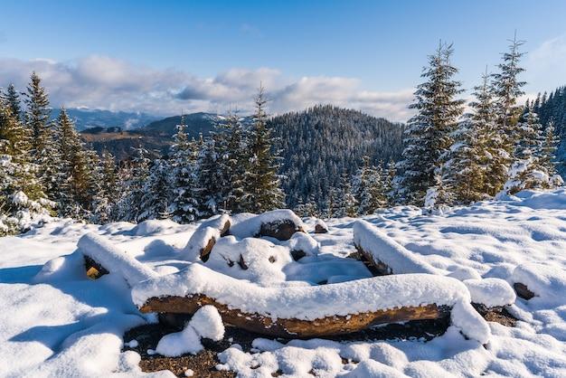 Een groot besneeuwd kampvuurplaats in de karpaten i felle koude zon