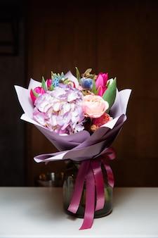 Een groot boeket kleurrijke bloemen van verschillende soorten in een transparante glazen vaas