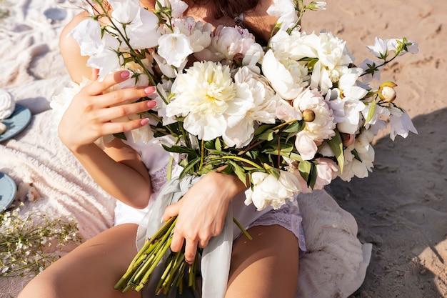 Een groot boeket pioenrozen en witte bellen in de handen van een meisje in een lichte jurk