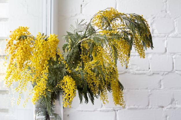 Een groot boeket van mimosa's tegen een witte bakstenen muur.