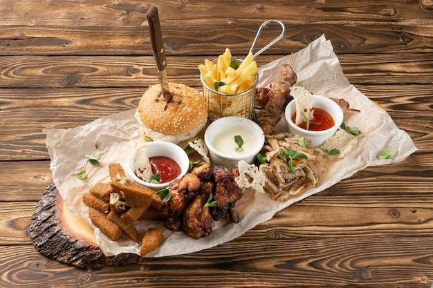 Een groot bord met biersnacks. hamburger, frites, varkens- en kipspiesjes, gekookte varkensoren, roggebroodkruimels met knoflook en drie soorten sauzen.