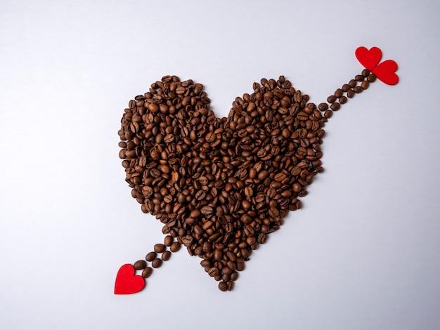 Een groot bruin hart gemaakt van koffiebonen en een bruine pijl met rode hartvormige punten doorboort het tegen een helder wit
