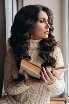 Een groot close-upportret van een warme sfeer, jonge mooie vrouw droomt bij het raam, leest een boek. getinte kleur.