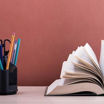 Een groot dik boek met de pagina's uitgespreid als een waaier en een standaard met pennen