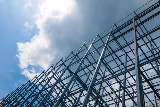 Een groot gebouw van staalstructuur in de hemel met zon en wolken.