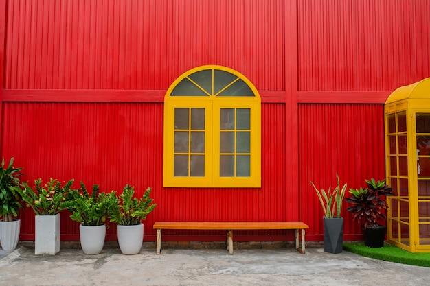 Een groot geel raam, bloempotten met planten en een bankje tegen een rode metalen muur in een stadsstraat. detailopname