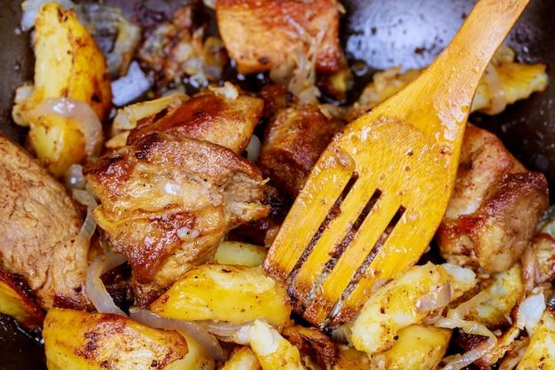 Een groot gegrild varkensvlees geserveerd in een pan met ui, geroosterde aardappelen
