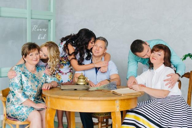 Een groot gezin met bejaarde ouders verzamelden zich samen aan een tafel, ze kusten elkaar. lunch, diner met familie, elke dag vakantie.