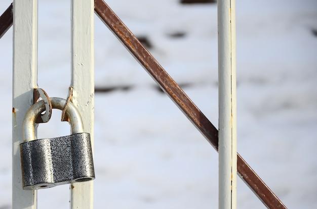 Een groot grijs hangslot hangt op een metalen hek