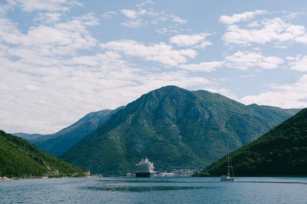 Een groot hoogbouw cruiseschip in de verige strait, in de boko kotor-baai in montenegro, tegen de achtergrond van de stad perast
