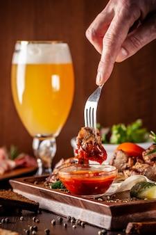 Een groot houten bord met een kebab van rundvlees, varkensvlees en kip.