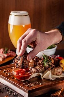 Een groot houten bord met een kebab van vlees.